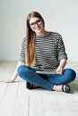 Taking time to relax beautiful young woman in striped clothing sitting on the floor and smiling Stock Photography