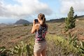 Taking vacation photos pretty young adult traveler visits tenerife canary islands spain volcanic mountains and rural area during Royalty Free Stock Photo