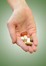 Taking daily vitamins or supplements hand holding medication on green background Stock Photo