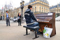 A talented homeless musician plays the piano in the street paris mar to earn some money on march paris france Royalty Free Stock Photo