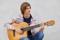Talented teenage boy with trendy hairdo wearing shirt and jeans holding acoustic guitar playing his favourite songs while sitting Royalty Free Stock Photo