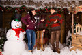 Talking couple surrounded with christmas decors young in winter outfits inside the wooden house various attractive beside big Stock Photos