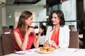 Talking and gossiping two girlfriends meet at café for breakfast Stock Image