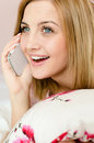 Talking on the mobile cell phone happy smiling charming young blond woman lying in bed holding pillow portrait of beautiful Stock Images