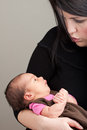Talking to her newborn baby a being held in the arms of mother Royalty Free Stock Photos