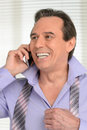 Talking to his loved ones cheerful mature businessman dressing up and at phone Royalty Free Stock Photography