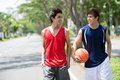 Talking young sportsmen two basketball players walking in the park Royalty Free Stock Image