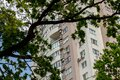 tall apartment building among trees leaves