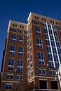 Tall brick building with blue tinted windows coverd on two sides with crisp blue sky clear Royalty Free Stock Photo