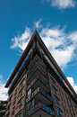 Tall building with angled roof against the blue sky Stock Image