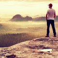 Tall man in white shirt and  black trousers with red baseball cap  stay on sharp cliff and watch to valley. Colorful  misty mornin Royalty Free Stock Photo