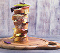 Tall sandwich of bread, sausage, cheese, basil Royalty Free Stock Photo