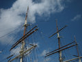 Tall ship masts the of a with blue sky and clouds in the background Royalty Free Stock Photos