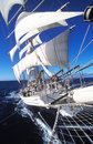 Tall ship at sea with its white sales gleaming in the sunlight as it sails through the calm blue ocean Royalty Free Stock Photo