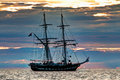 Tall ship at sunset a twin masted against coloured clouds Royalty Free Stock Photos