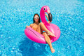 Tan girl sits on inflatable mattress flamingos and relax in the pool. Pool party