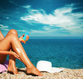 Tan woman applying sunscreen on legs lotion her sexy at beach Royalty Free Stock Photos