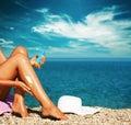 Tan woman applying sunscreen sulle gambe Fotografie Stock Libere da Diritti