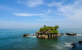 Tanah lot temple in bali at the sunny day is a rock formation off the indonesian island of it is home to the Royalty Free Stock Photos