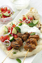 Tandoori lamb kebabs with naan bread salad and minted yogurt Stock Photo