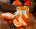 Tangerine jam in glass jar with fruit around Stock Images
