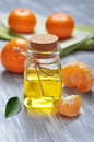 Tangerine oil in a glass bottle with fresh �� wooden background Royalty Free Stock Photography