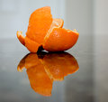 Tangerine peel a torn and its reflection on a granite surface Stock Image