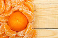 Tangerine with slices on wooden surface Royalty Free Stock Image
