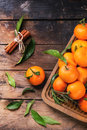 Tangerines with cinnamon leaves and stick on old wooden table top view Royalty Free Stock Photography