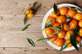 Tangerines or mandarins with green leaves on vintage wooden table from above in flat lay style.