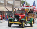 Tangier shriners in jalopy in parade in small town america shriner clowns car a summer with flags and ladder Royalty Free Stock Photo