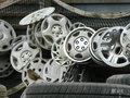 Tangle of hubcaps on a fence vehicle hooked in junkyard Stock Photography