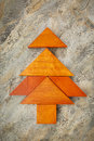 Tangram christmas tree abstract picture of a built from seven wooden pieces over a slate rock background holiday concept Stock Photo