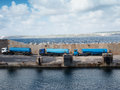 Tankers lined up on a cement wharf or dock pier at the side of harbor waiting to refuel ship or offload cargo Royalty Free Stock Photography