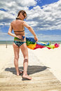 Tanned girl in bikini posing on the beach with colored pareos amid cloudy blue sky Royalty Free Stock Photography