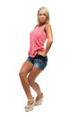 Tanned girl is dancing in denim shorts isolated on white background Stock Photos