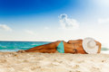 Tanned woman laying on white sand beach with tan wearing striped swimwear and big hat Royalty Free Stock Photography