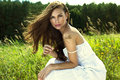 Tanned woman in white summer dress beautiful young with flowing brown hair green meadow Royalty Free Stock Photos