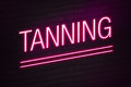 Tanning parlour neon sign pink with text on wall Royalty Free Stock Image
