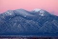 Taos mountain after sunset the sky over the snow covered sangre de christo mountains lights up pink in the minutes is the symbol Stock Photos