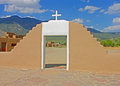 Taos pueblo church with cross wall and mountains Stock Photography