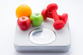 Tape measure on bathroom scale for weight of human body, dumbbells for fitness and fresh fruits. Concept of healthy lifestyle and Royalty Free Stock Photo