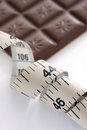 Tape measure and chocolate bar a with a defocussed in the back ground symbolic of diets temptation Royalty Free Stock Photo
