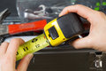 Tape measure horizontal photo of female hands pulling used out with old toolbox in background Stock Image