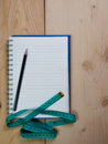 Tape measure with notebook for writing notes Royalty Free Stock Photo