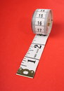 Tape measure a rolled up white with both inches and centimetres on a red paper background Royalty Free Stock Photo