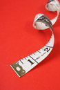 Tape measure a rolled up white with both inches and centimetres on a red paper background Royalty Free Stock Images