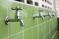 Taps in a row on green tiles Stock Photos