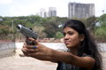 Target point a teenage indian girl aiming a gun carefully on a on a high altitude Royalty Free Stock Photos