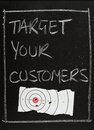 Target your customers written in white chalk on a blackboard next to a piece of a shooting with bullet holes a concept for Royalty Free Stock Image